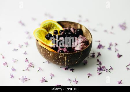 Gesunde smoothie Frühstück in Coconut Platte mit lila Blumen auf weißem Hintergrund - Stockfoto