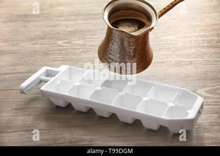 Das Gießen von Kaffee aus jezve in Eis Fach auf Tisch - Stockfoto