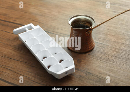 Jezve mit Kaffee und Eis Fach auf Tisch - Stockfoto