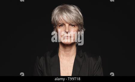 Ältere Frau mit weißen Haaren auf Kamera. Nahaufnahme der Frau in formale Abnutzung auf schwarzem Hintergrund isoliert. - Stockfoto