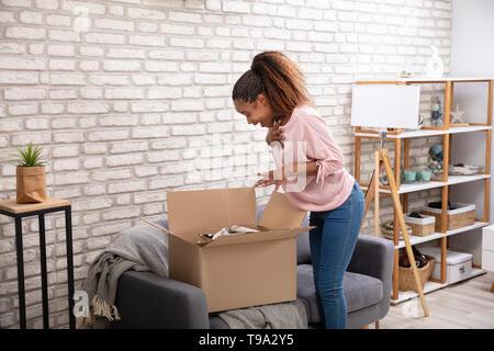Glückliche Frau Öffnen der Paketbox zu Hause - Stockfoto