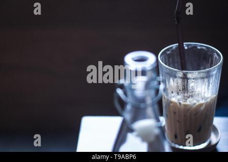 Iced Coffee Latte mit Eis auf Holz Tisch vintage Wasser klar blur Vordergrund mit Platz für Text. - Stockfoto