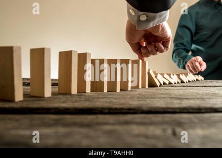 Geschäftsmann, stoppen den Domino-Effekt der fallenden Holzklötzen, eingeleitet durch einen Kollegen oder Business Wettbewerb in einem Konzept des Erfolgs und zur Problemlösung p - Stockfoto