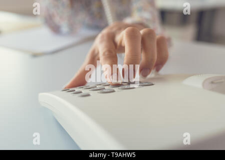 Detailansicht der Rezeptionistin Wählen einer Telefonnummer mit weißen Festnetztelefon. - Stockfoto