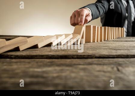 Hand der Geschäftsmann stoppen fallende Dominosteine. Enthält textfreiraum Holztisch. - Stockfoto