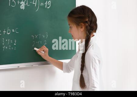 Süße Mädchen schreiben auf der Schiefertafel im Klassenzimmer - Stockfoto