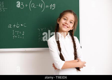 Süße Mädchen stehen in der Nähe der Tafel im Klassenzimmer - Stockfoto