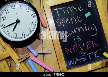 Zeitaufwand für das Lernen ist nie eine Verschwendung auf Phrase bunte handgeschrieben auf schiefertafel und Wecker mit Motivation, Inspiration und Bildung Konzepte. - Stockfoto