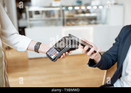 Unternehmer zahlen mit kontaktlosen Smart Phone, während im Cafe sitzen, Nahaufnahme - Stockfoto