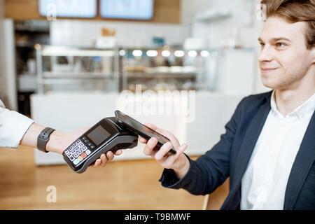 Junge Unternehmer kontaktloses Bezahlen mit Smart Phone, während im Cafe sitzen - Stockfoto