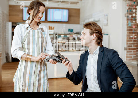 Junge Unternehmer mit hübschen Kellnerin im Cafe, kontaktlos mit smart phone - Stockfoto