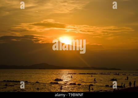 Strand Sonnenuntergang mit Silhouette Menschen Sandstrand auf der tropischen Insel Sommer bunte goldene Stunde Himmel mit Sonne über Berg Hintergrund