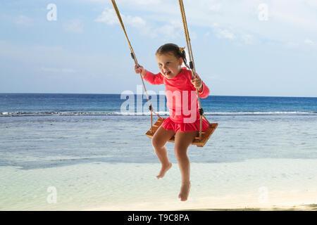 Portrait Of Happy Kleinkind Mädchen Schwingen am Strand unter den Baum. - Stockfoto