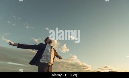 Ansicht von unten der junge Geschäftsmann im Anzug genießt seine Freiheit und berufliche Unabhängigkeit mit Arme weit offen stehen unter Abendhimmel. - Stockfoto