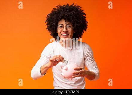 Lächelnd african-american man Geld in seinem sparschwein - Stockfoto