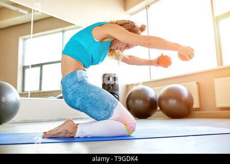 Junge attraktive Frau Yoga im Fitnessraum. Natürliches Licht ambient. - Stockfoto
