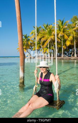 Frau genießt Swing in tropischen Gewässern und Palapa Plattformen,Lange Coco Plum Caye, Belize - Stockfoto