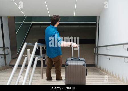 Mann mit Carry on Roller auf der Treppe - Stockfoto