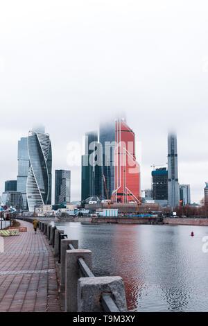 Nebel - fallen Wolkenkratzer von Moskwa City (MIBC) neben dem Fluss Moscva während einer Moody und nebligen Wintertag in Moskau (Moskau, Russland, Europa) - Stockfoto