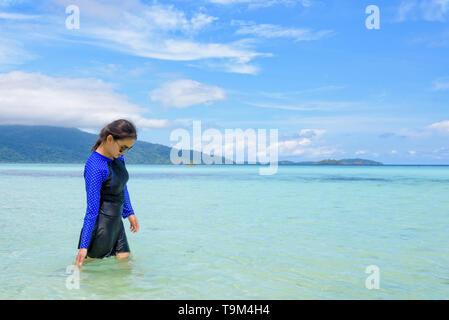 Asiatische Frau in Blau Badebekleidung und Sonnenbrillen zu Fuß im Meer und Strand mit Blick auf das klare Wasser im Sommer sky bei Ko Ra Wi, Reisen nach Koh Lipe Isla - Stockfoto