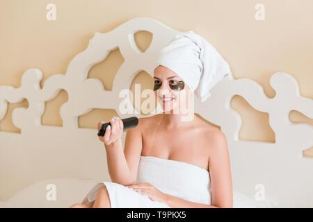 Schöne junge Frau mit unter Auge Patches und die TV-Fernbedienung in Bademantel im Bett lag. Happy girl kümmert sich um sich. Beauty pflege und gut - Stockfoto