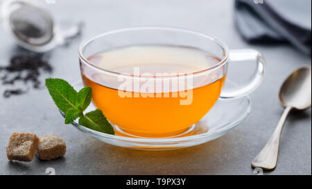 Tasse Tee mit Minze Blatt. Grauer Hintergrund. Close Up. - Stockfoto