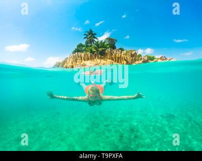 Geteilte Ansicht der weiblichen Apnoe unter Wasser und paradiesische Landschaft von St. Pierre Island Coral Reef auf den Seychellen. Schnorcheln Frau Erkundung Sealife von - Stockfoto
