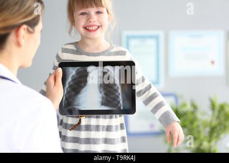 Ärztin Prüfung kleines Mädchen mit ultra-modernen Scanning tablet pc Gerät closeup - Stockfoto
