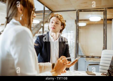 Junger Mann und Frau, die ein ernstes Geschäft Gespräch, Arbeit mit Papierdokumenten und Computer im Büro - Stockfoto
