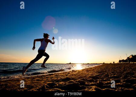 Junge Athleten entlang des Wassers edge bei Sonnenuntergang laufen, St Kilda, Melbourne, Victoria, Australien. - Stockfoto