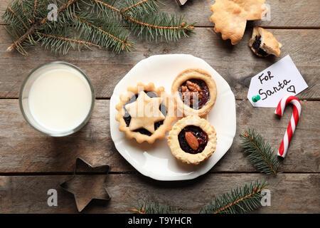 Teller mit leckeren Torten und Glas Milch auf holztisch Mince - Stockfoto