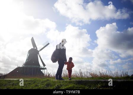 Asiatische Vater und seinem jungen Sohn hinter einer holländischen Windmühle in Zaanse Schans in den Niederlanden - Stockfoto