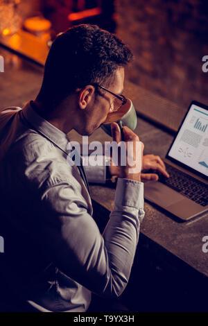 Geschäftsmann trinken Cappuccino und Arbeiten am Laptop - Stockfoto