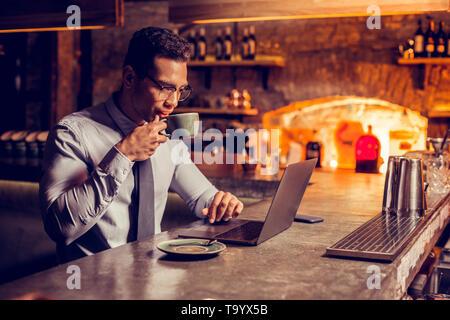 Geschäftsmann etwas Kaffee trinken während der Arbeit am Laptop - Stockfoto