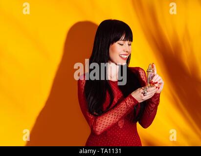 Shopper Frau im roten Kleid auf gelbem Hintergrund mit Schatten. Die glückliche Dame mit Parfüm Flasche, kopieren. - Stockfoto