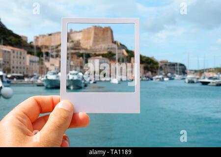 Nahaufnahme eines jungen kaukasischen Mann am Hafen von Bonifacio, Korsika, Frankreich, mit einem weißen Rahmen in seiner Hand Framing der berühmten Zitadelle, Simulieren eines - Stockfoto
