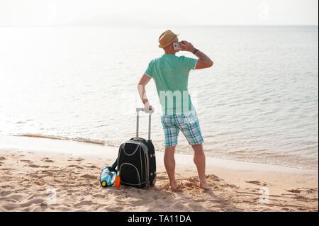 Natur reisen Personen Konzept - Mann stand in der Nähe vom Meer am Strand mit Koffer und sprechen über das Telefon - Stockfoto