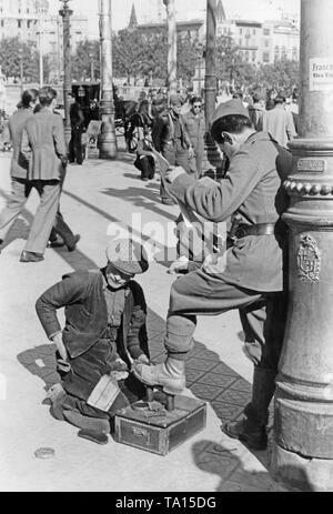 Ein spanischer Soldat lässt einen Mann sauber seine Schuhe, während er eine Zeitung lesen, vor einer Laterne auf der Rambla (Promenade im Zentrum) in Barcelona?? Katalonien, Spanien im März 1939, nach der Eroberung der Stadt durch General Francisco Franco im Januar, 1939. Im Hintergrund, flaneure und Soldaten. Auf der Laterne, einen Anruf von Franco für die Einwohner von Barcelona. Unten auf dem gusseisernen Laterne, das Wappen von Barcelona. - Stockfoto