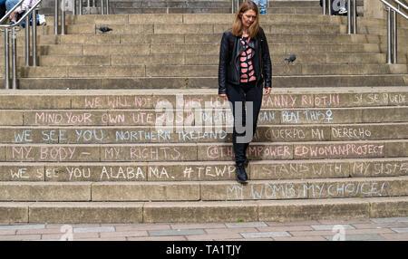 Frau geht nach unten Schritte in feministische Graffiti der Glasgow Royal Concert Hall in Glasgow, Schottland, UK abgedeckt - Stockfoto