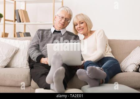 Moderne Großeltern. Senior Paar Surfen auf dem Laptop - Stockfoto