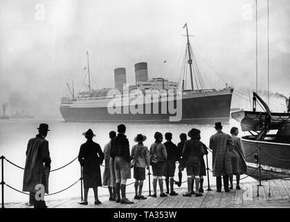Der Ocean Liner 'Mauretania' erreicht den Hafen von London nach ihrer ersten Reise nach New York über die Themse. Die 'Mauretania' war das größte Schiff, das jemals die Themse gesegelt. - Stockfoto