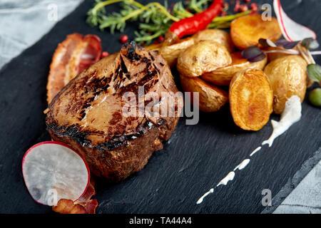 Rindersteak mit gebackenen Kartoffeln und Gemüse, schwarzer Hintergrund, close-up. Konzept essen. - Stockfoto