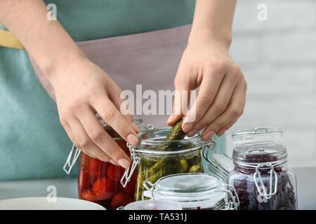 Frau mit leckeren fermentiertes Gemüse in Gläsern auf dem Tisch - Stockfoto
