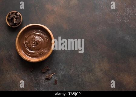 Nutella auf dunklem Hintergrund, Ansicht von oben, kopieren. Hausgemachte geschmolzene Schokolade in der Schüssel. - Stockfoto