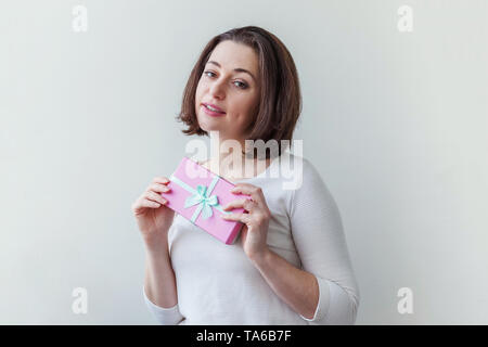 Junge positive Frau mit kleinen rosa Geschenkverpackung auf weißem Hintergrund. Vorbereitung für den Urlaub. Mädchen suchen glücklich und aufgeregt. Weihnachten birt - Stockfoto