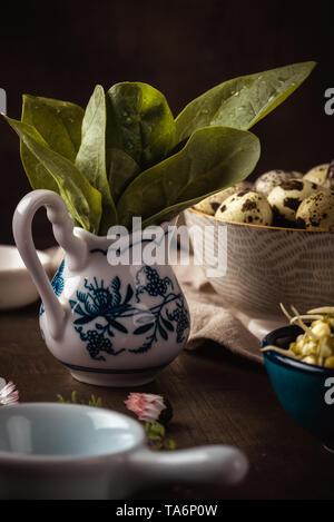 Vertikale Foto von mehreren Schalen auf dunklem Holz. Schalen enthält mung Sojasprossen, grüne Spinat und beschmutzt Wachteleier. Schalen haben verschiedene Farbe