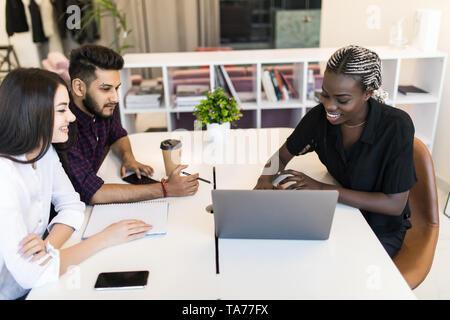 Schwere afrikanische team leader erklärt online Projekt auf Laptop auf diverse Mitarbeiter, fokussiert drei Mitarbeiter im Büro Planung gemeinsam anhören - Stockfoto