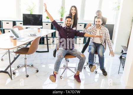 Unbeschwert aufgeregt diverse Arbeitnehmer Spaß reiten oh Stühle Freitag gemeinsam feiern, glückliche Mitarbeiter genießen Sie lustige Wettbewerb gemeinsam lachen Fe - Stockfoto