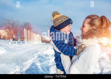 Eine junge Mutter, eine Frau mit einem Kind, ein Junge, ein Sohn der 3 Jahre alt, im Winter draußen in warme Kleidung, Spielen, Spaß haben, relaxen am Wochenende in
