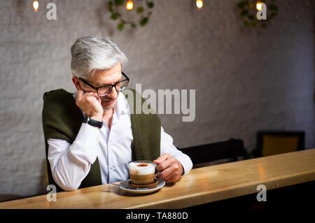 Nachdenklich, älterer Mann mit einem Kaffee in der Bar - Stockfoto